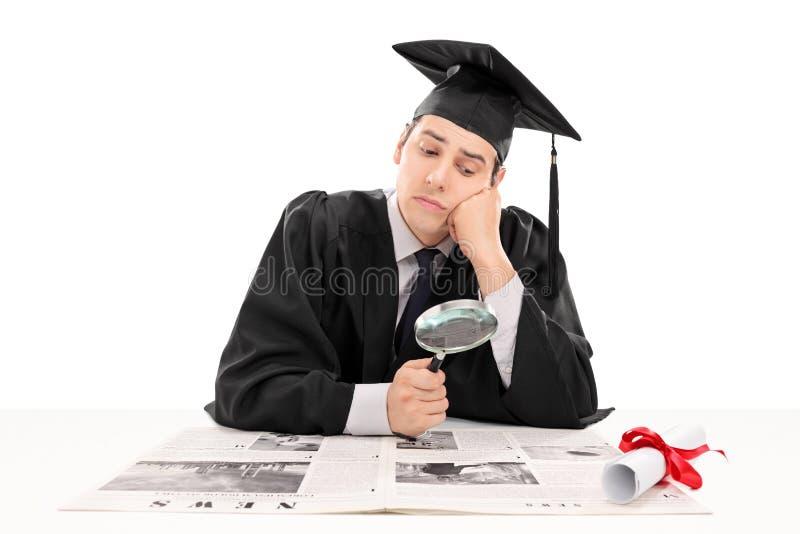 Aluno diplomado que procura pelo trabalho nos papéis foto de stock royalty free