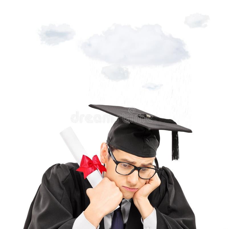 Aluno diplomado triste que guardam o diploma e uma nuvem que flutua sobre h imagens de stock