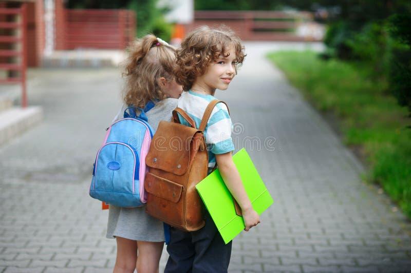 Aluno dois pequeno da escola primária, menino e menina, suporte que junta-se às mãos imagens de stock
