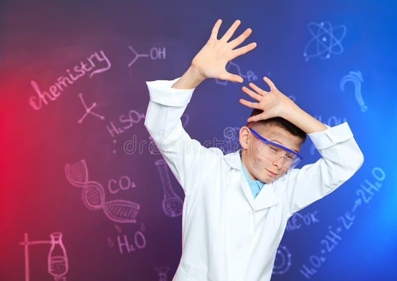 Aluno emocional que protege-se contra o quadro-negro com fórmulas escritas da química fotos de stock