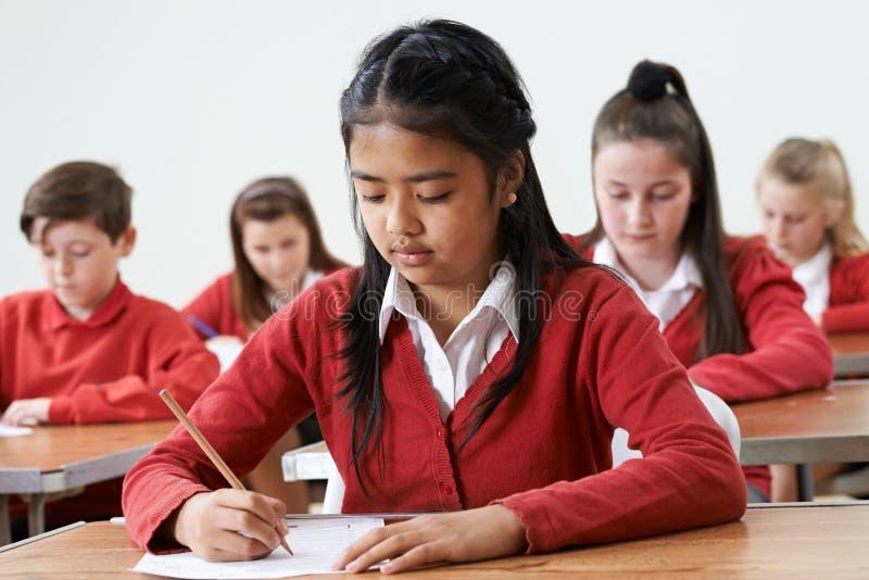 Aluno fêmea na mesa que toma o exame da escola imagem de stock