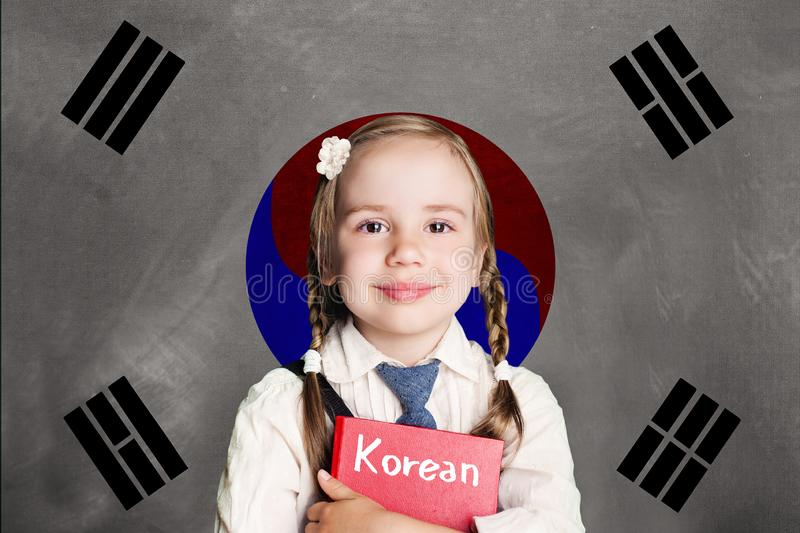 Aluno feliz da menina da criança com o livro contra o fundo da bandeira de Coreia do Sul Aprenda a língua coreana, conceito de Co fotografia de stock royalty free