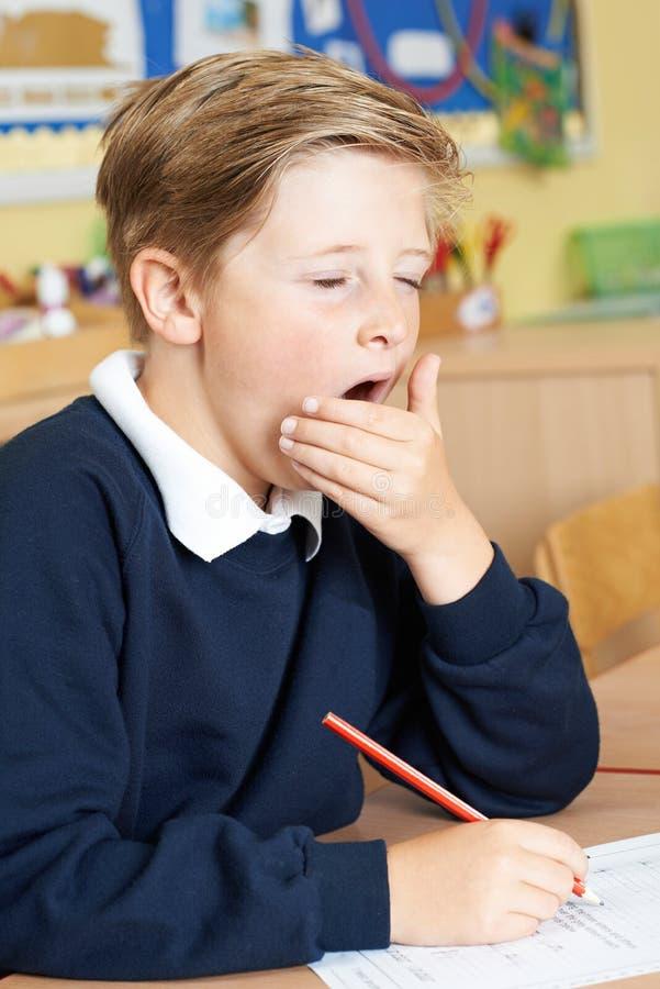Aluno masculino da escola primária que boceja na sala de aula imagem de stock royalty free