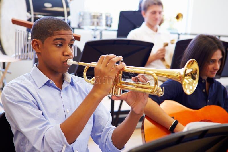 Aluno masculino que joga a trombeta na orquestra da High School fotografia de stock