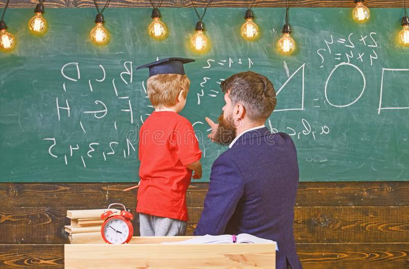 Aluno no tampão da graduação que resolve a equação com a ajuda do professor Aritmética de ensino da criança do homem ao apontar imagem de stock royalty free
