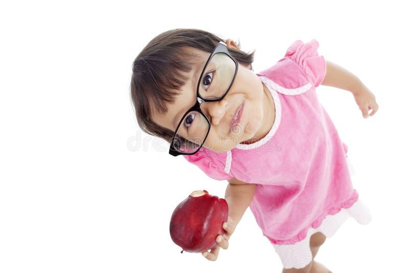Aluno pequeno que come a maçã imagem de stock