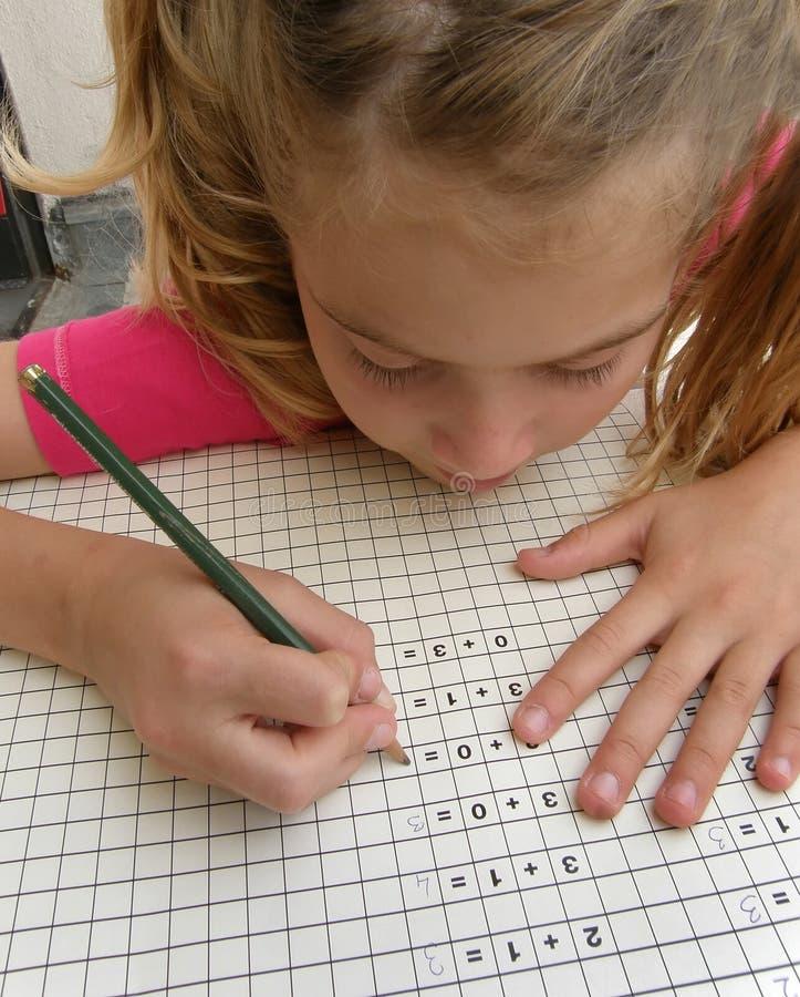 Aluno, trabalhos de casa writening da matemática da menina fotos de stock royalty free
