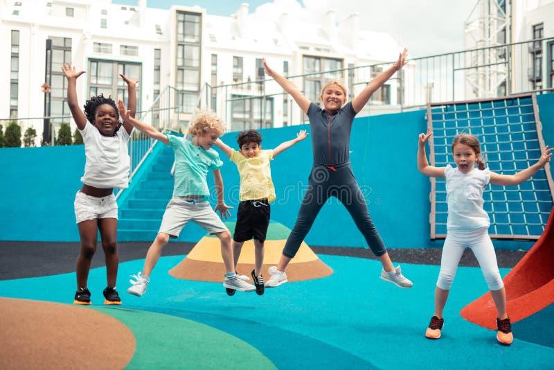 Alunos alegres que saltam para cima e para baixo em uma terra de esportes imagens de stock royalty free