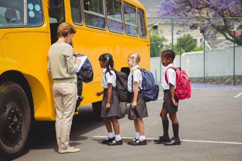 Alunos bonitos que esperam para obter no ônibus escolar fotos de stock