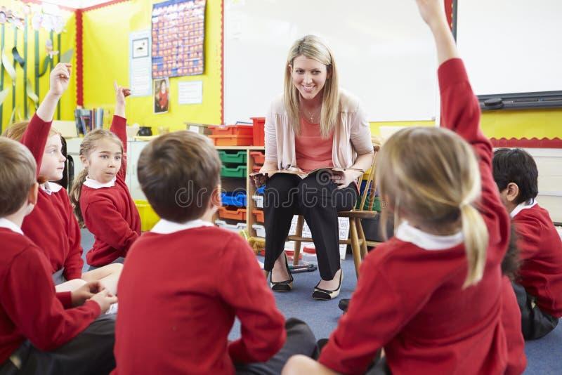 Alunos da escola primária de Reading Story To do professor fotografia de stock royalty free