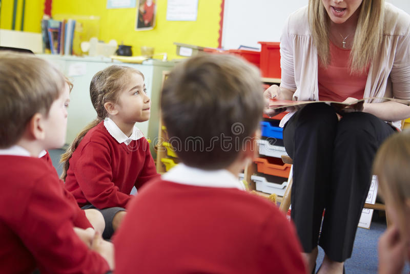 Alunos da escola primária de Reading Story To do professor fotos de stock royalty free