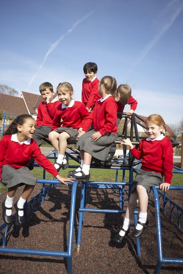 Alunos da escola primária no equipamento de escalada foto de stock