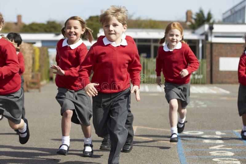 Alunos da escola primária que correm no campo de jogos foto de stock royalty free