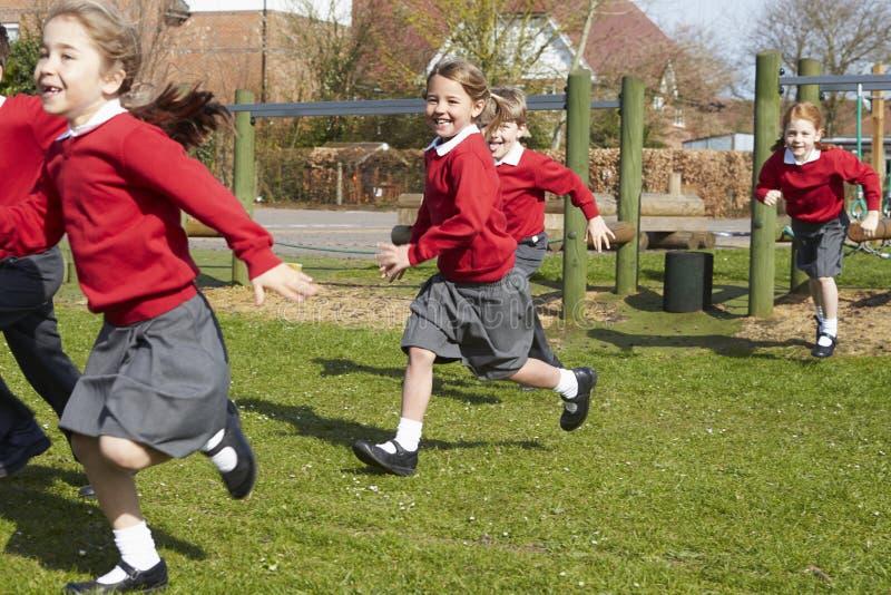 Alunos da escola primária que correm perto do equipamento de escalada fotos de stock royalty free