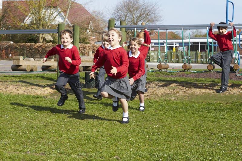 Alunos da escola primária que correm perto do equipamento de escalada fotografia de stock