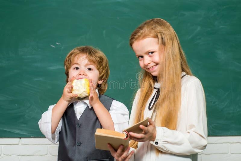 Alunos de sorriso felizes que tiram na mesa preschooler Copie o espa?o Escola prim?ria Escola e crian?as do livro De volta a foto de stock