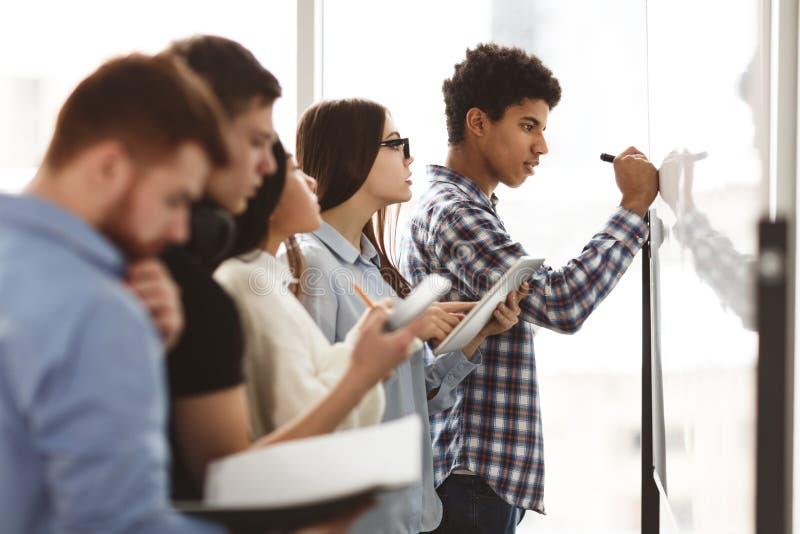 Alunos do ensino médio masculinos escrevendo em quadro branco na aula imagem de stock