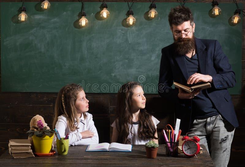 Alunos do professor e das meninas na sala de aula, quadro no fundo Conceito da escola primária O homem com barba ensina imagem de stock royalty free