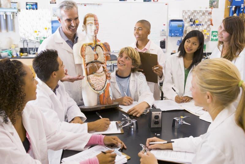 Alunos e seu professor na classe da ciência fotografia de stock