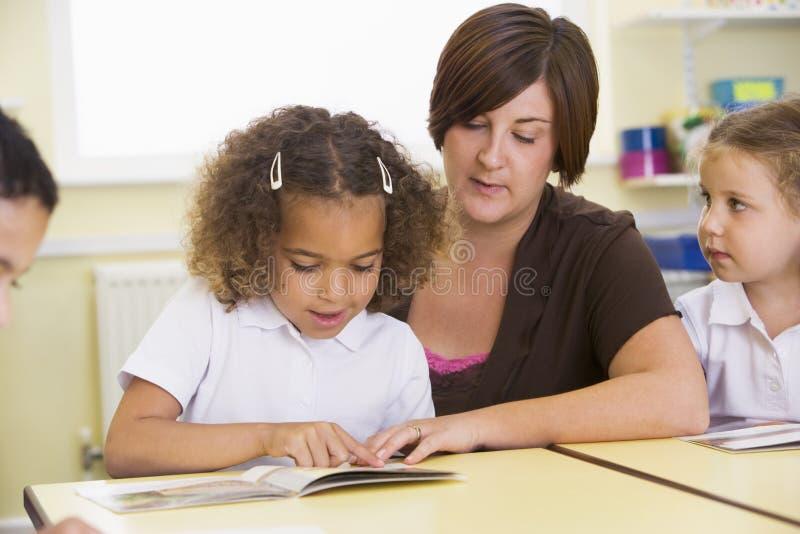 Alunos e sua leitura do professor na classe fotografia de stock