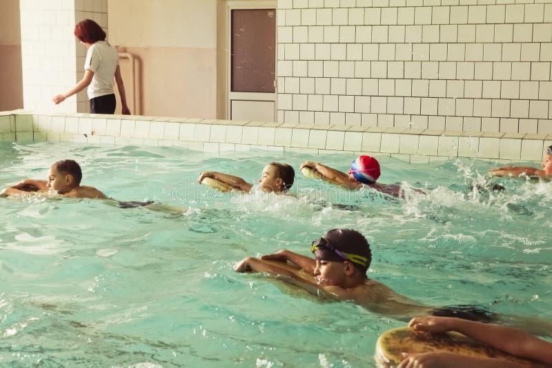 Alunos elementares dentro da lição nadadora das habilidades fotografia de stock royalty free