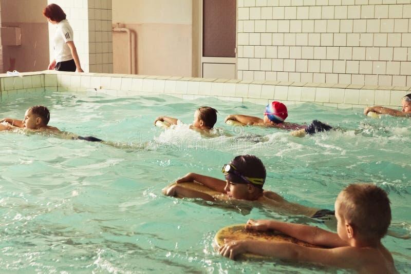 Alunos elementares dentro da lição nadadora das habilidades foto de stock royalty free