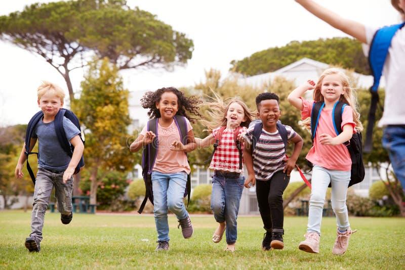 Alunos entusiasmados da escola primária que correm através do campo no tempo da ruptura fotografia de stock