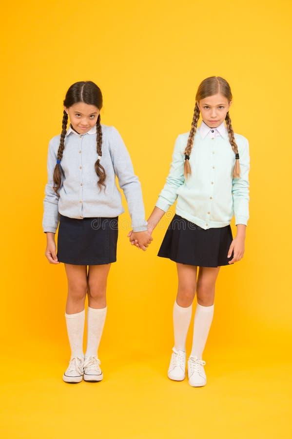 Alunos excelentes dos melhores amigos das estudantes Farda da escola arrumada da aparência das estudantes Amizade da escola setem imagens de stock