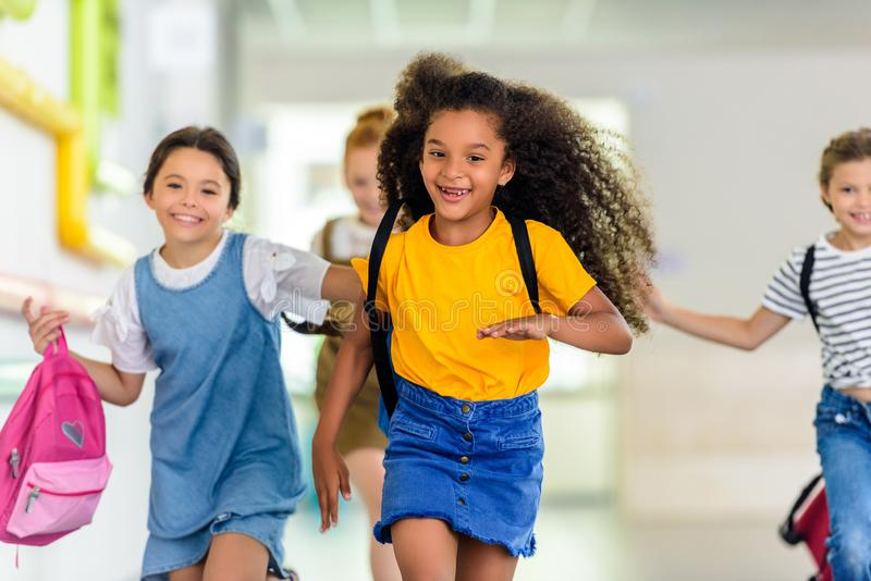 alunos felizes adoráveis que correm pela escola imagem de stock