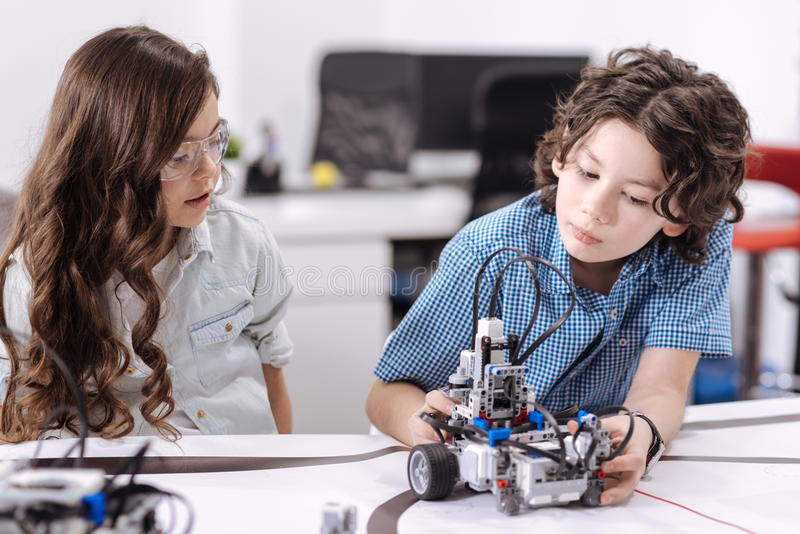 Alunos inquisidores que exploram o robô na escola imagem de stock royalty free