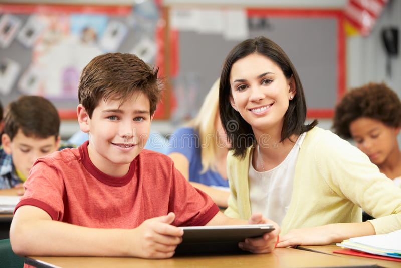 Alunos na classe que usa a tabuleta de Digitas com professor fotos de stock royalty free