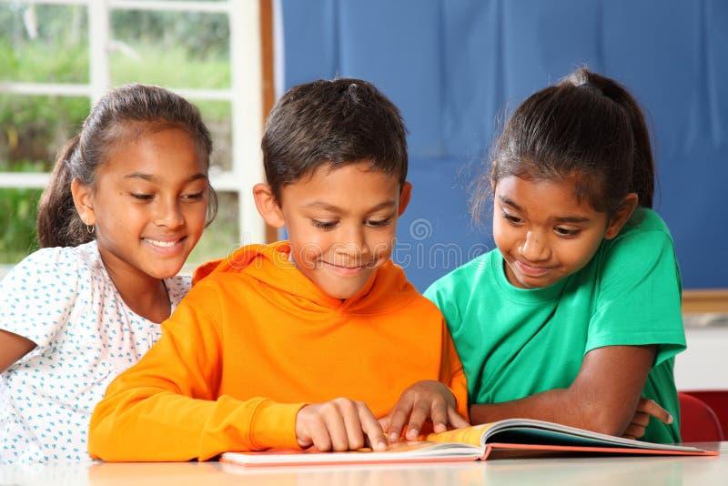 Alunos preliminares na aprendizagem da leitura da classe foto de stock