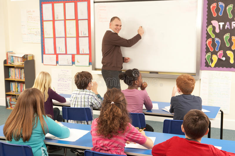 Alunos que estudam na sala de aula com professor fotografia de stock