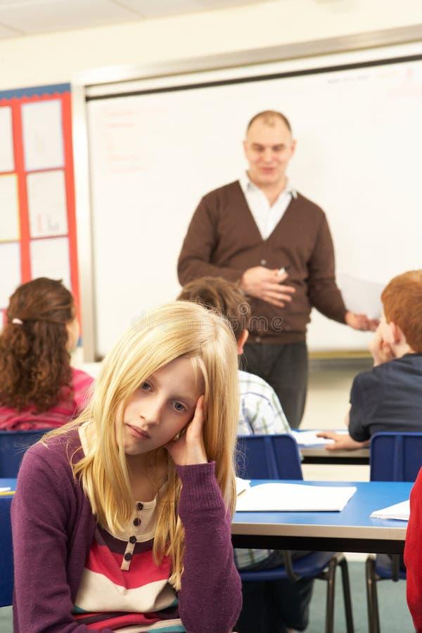 Alunos que estudam na sala de aula com professor imagens de stock