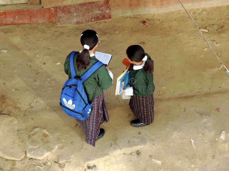 Alunos que leem na maneira à escola de preparar-se para exames foto de stock
