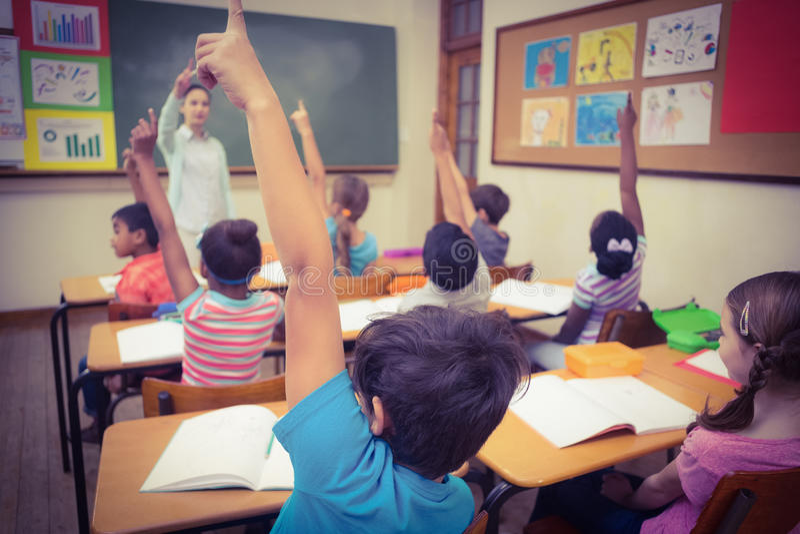 Alunos que levantam suas mãos durante a classe fotos de stock