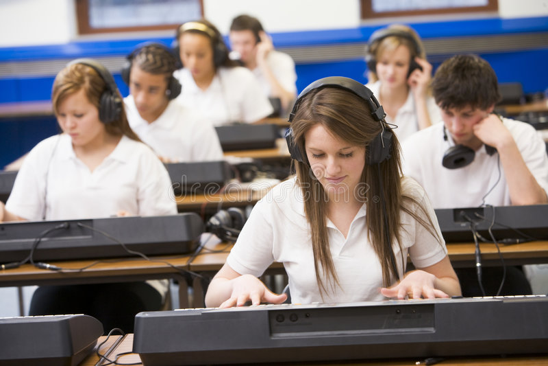 Alunos que praticam o teclado na classe de música fotografia de stock