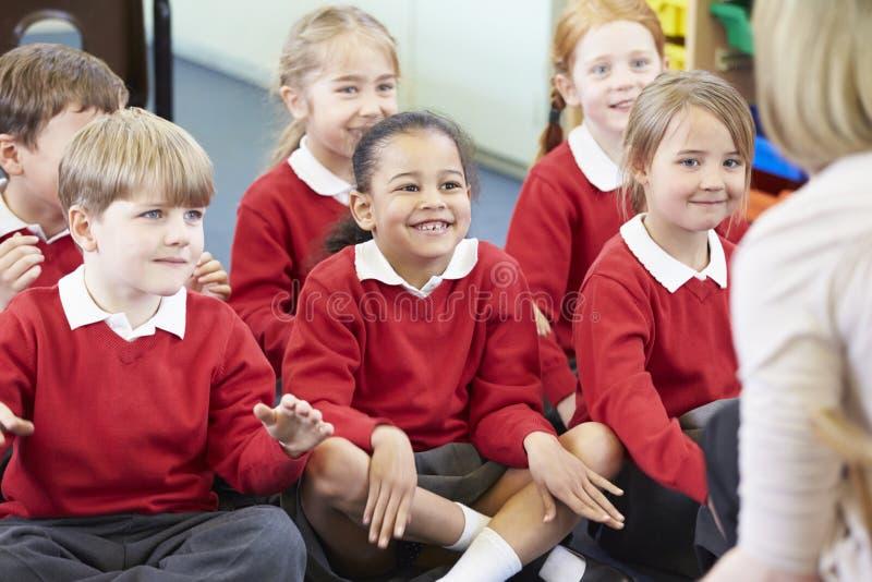 Alunos que sentam-se em Mat Listening To Teacher imagens de stock