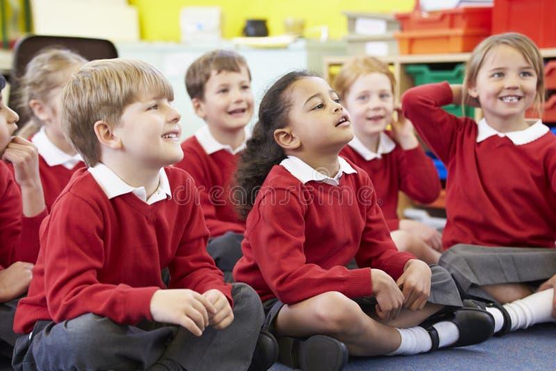 Alunos que sentam-se em Mat Listening To Teacher fotografia de stock
