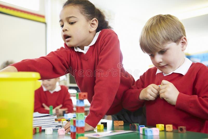 Alunos que trabalham com blocos coloridos na lição das matemáticas imagem de stock