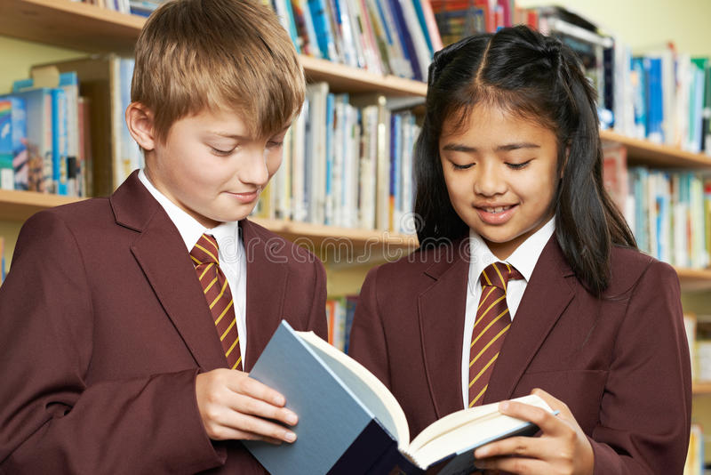 Alunos que vestem o livro de leitura da farda da escola na biblioteca foto de stock royalty free