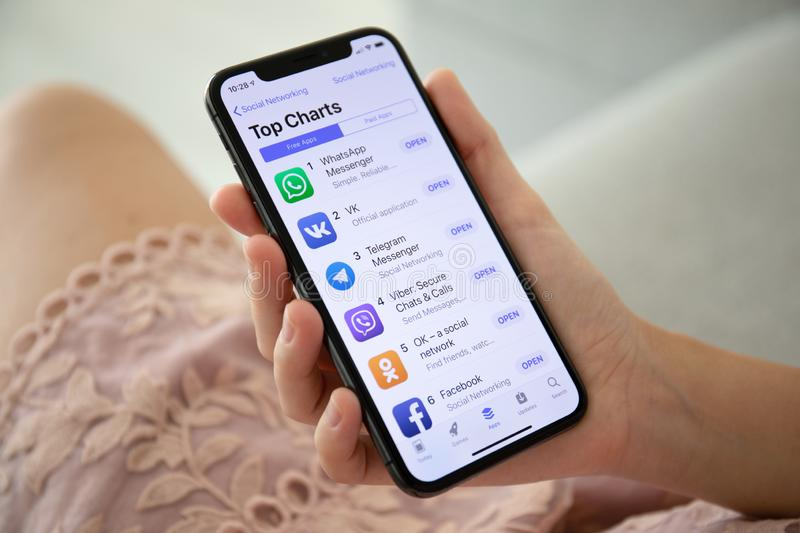 Woman holding iPhone X with social networking Messenger stock photo