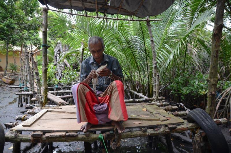 Aluthgama, Sri Lanka - 4 mai 2018 : L'homme sur un pilier en bois tient dans des mains un petit crocodile images stock