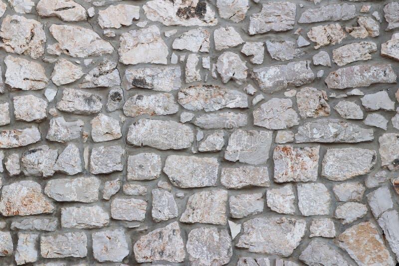 Alvenaria de pedra medieval antiga Textura de um fragmento de uma parede de uma estrutura velha Um fundo para o projeto e os trab fotos de stock