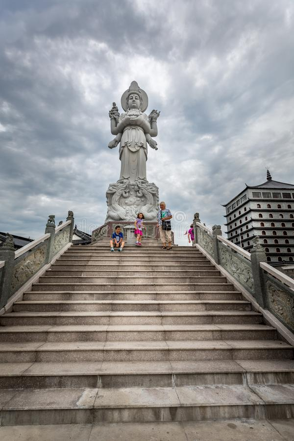 Low angle view of a family at Dragon Gate on stone steps next to a large Chinese statue with dramatic sky. stock photo