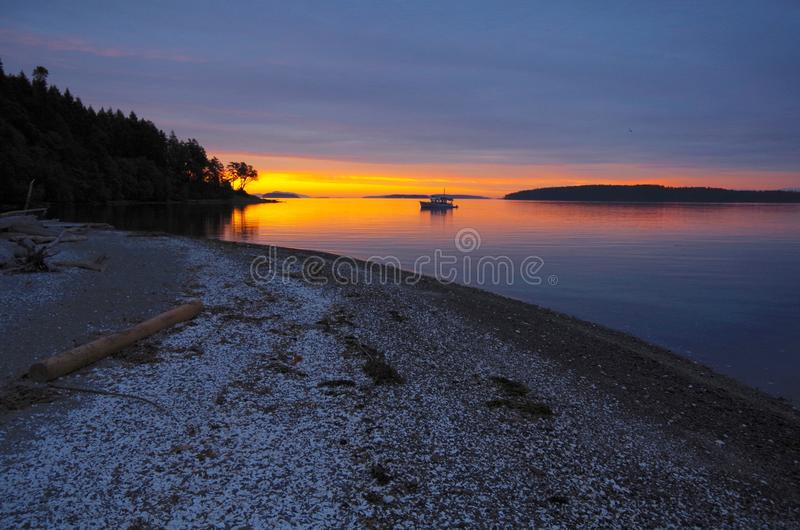 Alvorecer alaranjado incrível com a praia ancorada do iate e do shell imagem de stock