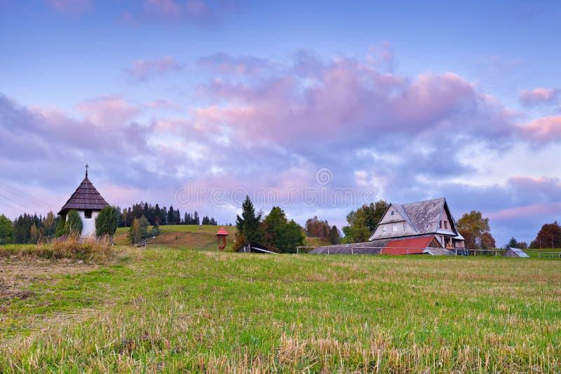 Alvorecer bonito com a casa na paisagem do upland imagem de stock royalty free
