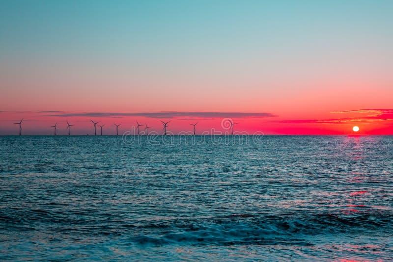 Alvorecer carmesim Turbinas da exploração agrícola de vento a pouca distância do mar da energia limpa em sunris imagem de stock royalty free