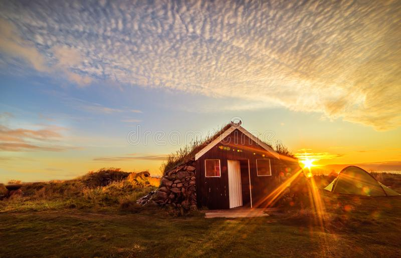 Alvorecer na costa do Oceano Atl?ntico Uma casa velha tradicional com um telhado coberto de vegeta??o com a grama e uma barraca n fotos de stock