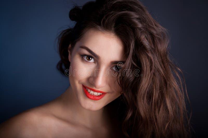 Alyona, cara de sorriso com olhos marrons, fundo azul fotografia de stock royalty free